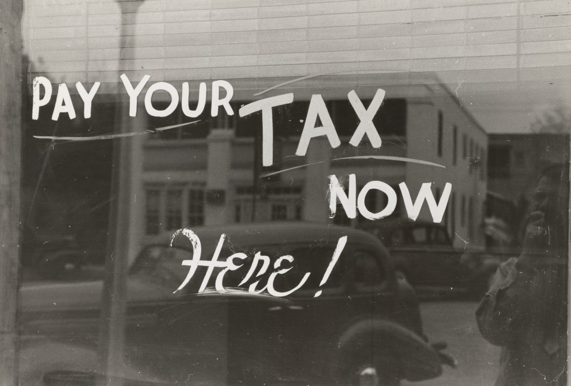 Pay your tax here now written on a window